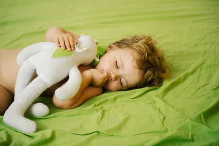 Cute baby boy child with blond curly hair sleeps peacefully with soft toy in bed on green sheet
