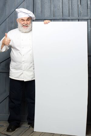 Cook holding blank paper on wooden background, copy space