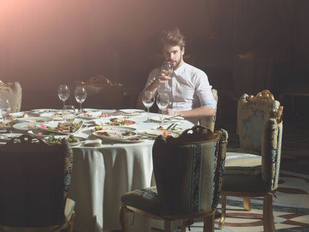 dirty blond: Handsome young man with beard and blond hair drinks wine from glass sitting at table with leftovers or residues food on dirty plates after banquet dinner in restaurant