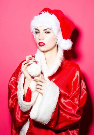poses de modelos: Pretty girl young beautiful cute woman sexy female model in traditional santa claus new year red hat and suit poses with Christmas bauble on pink background Foto de archivo