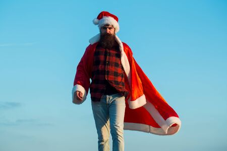 young handsome bearded bad santa claus man with long beard in checkered shirt jeans and red new year hat in christmas or xmas coat outdoor on blue sky background Stock Photo