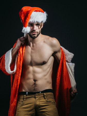 Handsome santa claus guy sexy young bearded macho christmas man model in red xmas or new year coat and hat has bare muscular torso and chest on black background