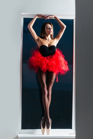 ballerina tights: Pretty sexy girl dancer young cute slim woman ballerina with long beautiful hair and legs in black fishnet tights pointe shoes and fashionable red tutu skirt at window on white wall background