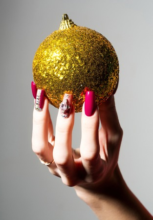 christmas manicure: Female hand with fingernail manicure holds beautiful golden sparkling Christmas bauble traditional xmas new year decoration ball on grey background