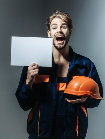 boilersuit: Excited man handsome builder construction mason worker repairman craftsman foreman blond bearded male in boilersuit keeps orange hard hat and paper for copy space in hands on grey background