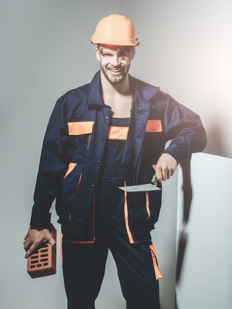 Happy man smiling handsome builder construction mason worker bricklayer in orange hard hat and boilersuit keeps brick and trowel on grey background Stock Photo