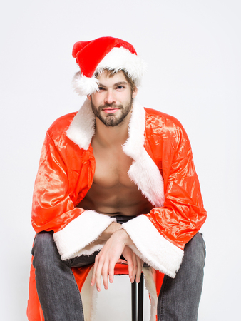 unbutton: Handsome man with beard or muscular macho athlete bodybuilder in santa hat and unbutton suit with six packs and abs on muscle torso sits isolated on white Stock Photo
