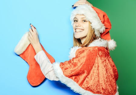 Cheerful pretty girl or cute beautiful woman female model in santa hat and suit with Christmas sock or stocking on blue and green background