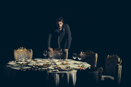 dirty blond: Handsome young man with beard and blond hair stands over table with leftovers or residues food on dirty plates after banquet dinner in restaurant on dark background Stock Photo