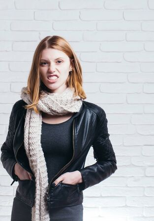 dissatisfied: Dissatisfied pretty girl or cute beautiful woman female model with red hair with knitted scarf wrinkles nose on white brick background Stock Photo
