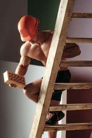 nackte brust: young handsome macho man builder with sexy muscular athletic strong body has bare torso and strong belly with six packs or abs in orange hard hat or helmet holds brick on wood ladder Lizenzfreie Bilder