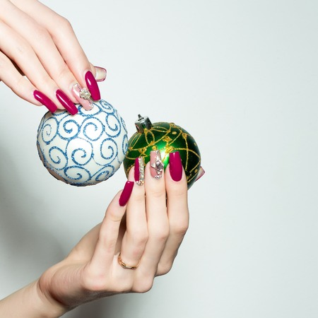 christmas manicure: Female hands with fingernail manicure hold beautiful blue and green Christmas baubles with ornament traditional xmas new year decoration balls isolated on white