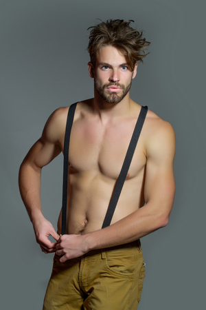 macho: Handsome guy fashion sexy young bearded macho man model with suspenders on pants has bare muscular torso holds on grey background Stock Photo