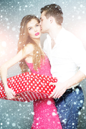 Beautiful fond young couple standing close to each other, holding big spotted red present box, vertical photo
