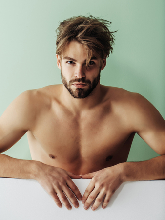 Handsome guy fashion sexy young bearded macho man model with bare muscular chest on green background