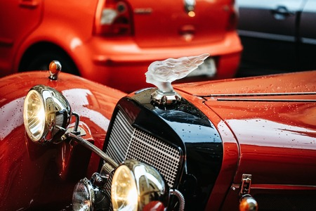 Old retro or vintage car or automobile front side red color classic vehicle with headlight lamps on parking