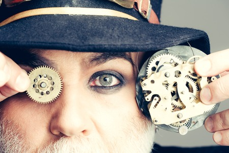 Senior man or watchmaker in black hat keeps cogwheel and mechanical metallic gears on grey wall