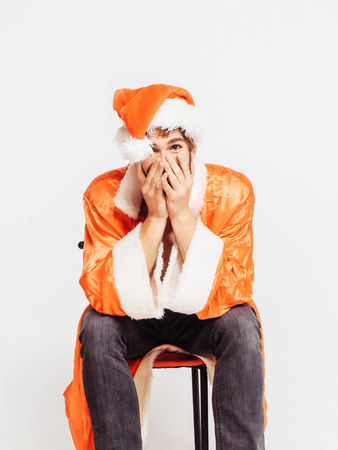 timid: Playful man shy handsome young male model in red santa claus hat and suit for Christmas or new year laughs timid hiding face with hands isolated on white Stock Photo