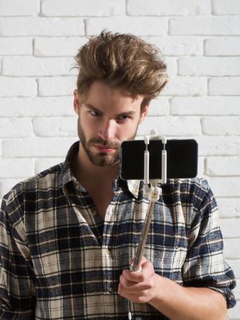 conferencing: Handsome man young blond bearded male model with beard in plaid shirt uses smartphone or mobile phone on selfie stick on white brick background Stock Photo