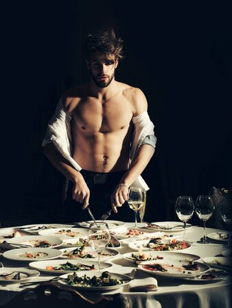 unbutton: Handsome man or sexy muscular macho athlete in unbutton shirt stands with fork and knife at table with leftovers or residues food on dirty plates after banquet in restaurant on dark background