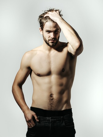 Handsome guy fashion sexy young bearded macho man model in pants with bare muscular torso and chest on grey background