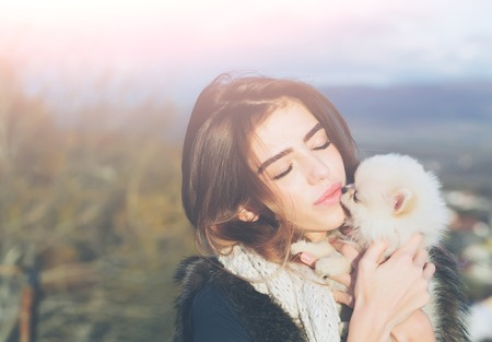 animal woman: pretty girl young beautiful woman in fur waistcoat and scarf holds cute small dog pet in hands outdoors on natural background