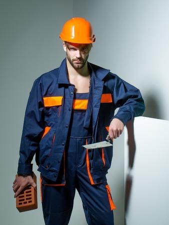 boilersuit: Handsome man builder construction mason worker bricklayer in orange hard hat and boilersuit keeps brick and trowel on grey background Stock Photo