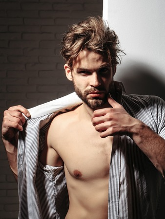 unbutton: Handsome man or muscular blond macho athlete bodybuilder with six packs and abs on muscle torso in unbutton shirt touches beard on white background Stock Photo