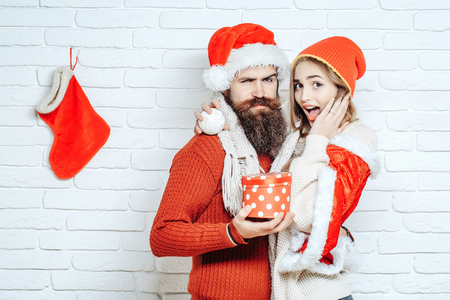 Young Christmas couple in red santa claus hats of bearded man hipster with gift box and amazed pretty sexy girl or beautiful woman on white brick wall