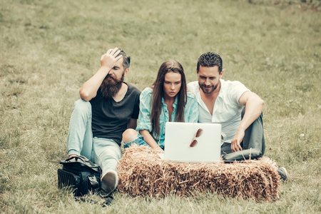 Frustrated friends sad people pretty girl and handsome men use laptop computer outdoors on natural background