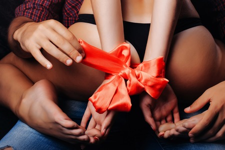 attractive female: man holding female sexy buttocks of young woman with slim body and legs with bare back in lingerie has red ribbon bow on hands