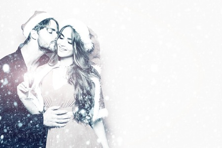 young christmas couple of santa claus bearded man in hat and pretty sexy girl in coat with smiling face on new year or xmas drinking champagne from glass under snow, copy space, black and white Stock Photo