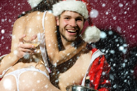 red corset: happy sexy new year couple of woman in corset and red christmas hat embracing muscular man in santa claus winter coat holding wine bottle in pail in on purple background under white snow and snowflakes Stock Photo