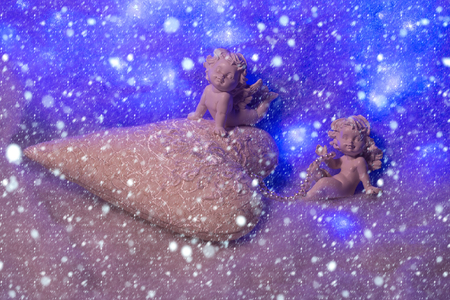 beautiful soulful figurine composition of cupid angels for valentine day or christmas with small pillow in shape of heart lying on white wadding decorating snow under snowflakes