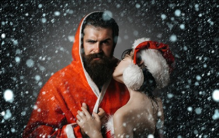 xmas couple of bearded handsome santa claus man in new year coat and pretty sexy girl in christmas hat on grey background under snow and snowflakes Stock Photo
