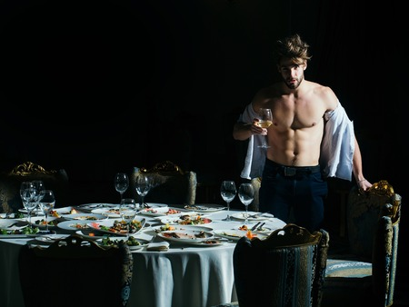 unbutton: Handsome man or sexy muscular macho athlete stands with wine glass in unbutton shirt over table with leftovers or residues food on dirty plates after banquet dinner in restaurant on dark background
