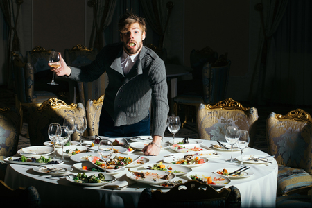 dirty blond: Surprised man handsome young male with beard and blond hair eats vegetables with wine in glass from dirty plates with leftovers or residues of food after banquet dinner on table in restaurant Stock Photo