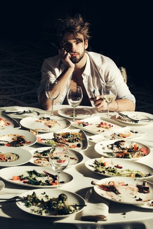 dirty blond: Handsome man with beard and blond messy hair bored or tired at table with leftovers or residues food on dirty plates after banquet dinner in restaurant on dark background