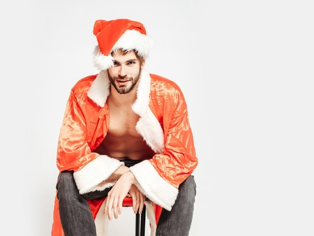 unbutton: Handsome man with beard or muscular macho athlete bodybuilder in santa hat and unbutton suit with six packs and abs on muscle torso sits copy space isolated on white