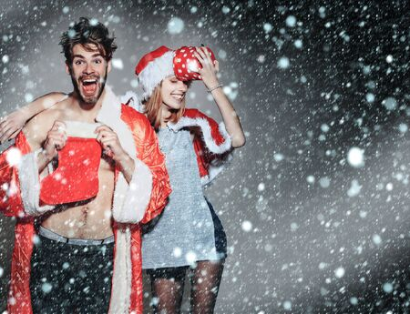 happy young couple of pretty cute girl or woman and handsome bearded man with bare muscular chest in santa claus coat and hat with new year sock and gift box on grey backdrop under snow