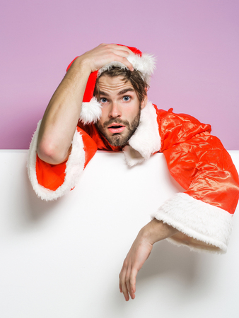 Handsome sexy bearded christmas man with beard on sad tired face in red santa claus hat and suit for xmas or new year celebration on white lilac background Stock Photo