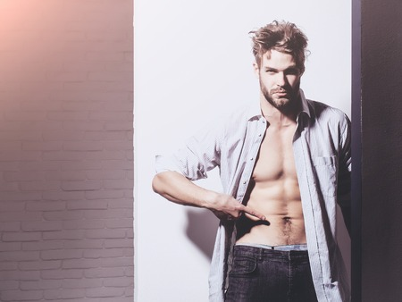 unbutton: Handsome man with beard or blond muscular macho athlete bodybuilder in unbutton shirt points to six packs and abs on muscle torso on white background