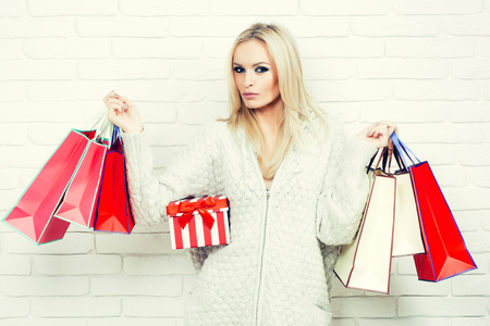 sexy sweater: Pretty girl or beautiful cute woman fashion model with blond hair in sexy knitted sweater with shopping bags and gift box on white brick wall Stock Photo