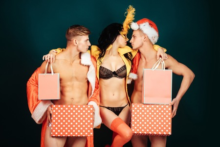 Pretty girl or beautiful woman in golden, carnival mask with feathers and sexy lingerie. Handsome, muscular men with muscle bodies in red santa suits with Christmas presents on blue wall Stock Photo