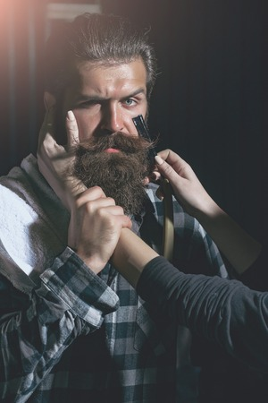 Female hands shave bearded man, handsome hipster, brunette with beard and moustache. Woman works with vintage razor on dark background