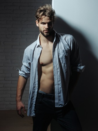 unbutton: Handsome man with beard or blond muscular macho athlete bodybuilder in unbutton shirt with six packs and abs on muscle torso poses on white background Stock Photo
