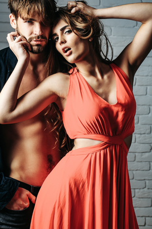 Sexy couple young beautiful cute lovers in love pretty girl has long hair in orange dress and handsome man with bare muscular torso white brick wall background