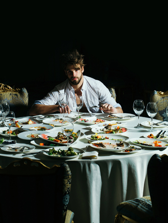 dirty blond: Handsome man with beard and blond messy hair eats with fork and knife at table with leftovers or residues food on dirty plates after banquet dinner in restaurant on dark background