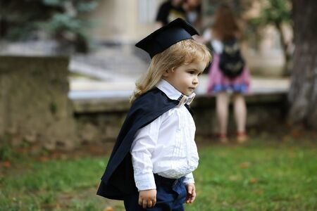 Little boy child in black academic gown and squared school hat with blonde hair standing on green grass outdoor on natural background