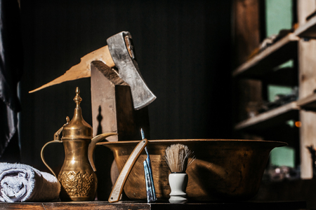 Vintage barber or shaver tools on wooden table. Old razor with cutthroat blade, copper basin, water jug, axe, shaving brush and towel in barbershop or hairdressing saloon Stock Photo